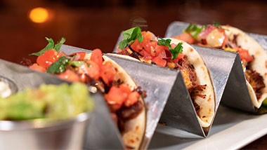 three tacos with pico de gallo on top with guacamole on the side